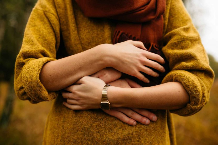 woman in yellow jumper being hugged
